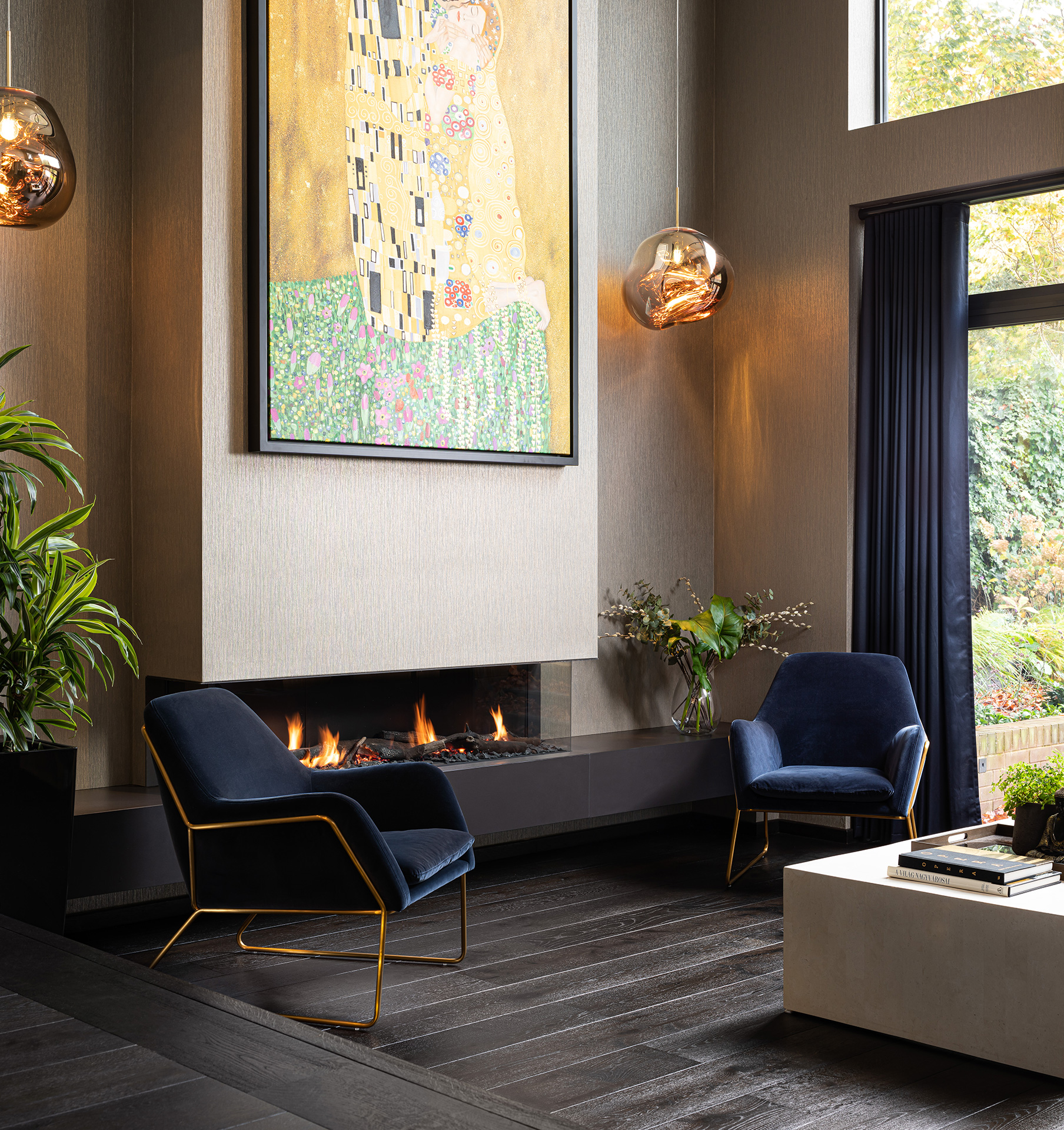 Angular deep blue chairs on dark wood floor in front of modern fireplace