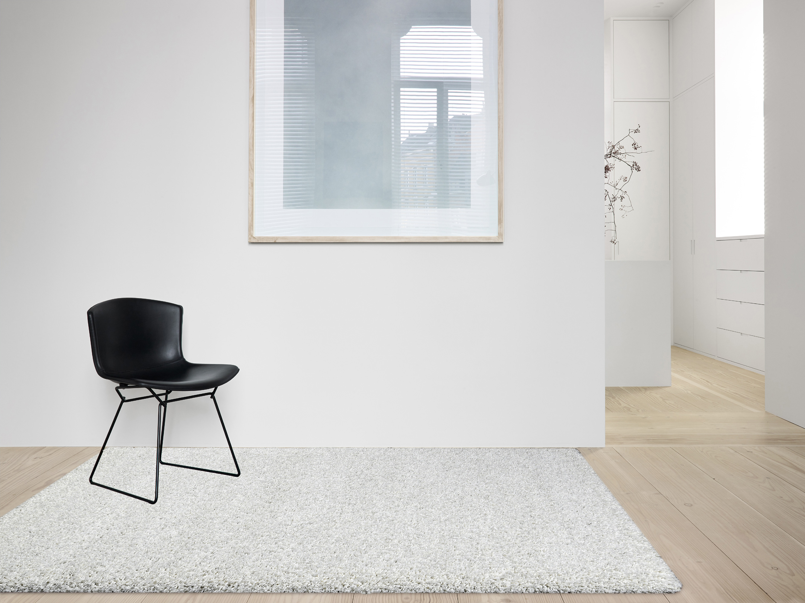 Twilight 6600 Snow White Square Rug in room with wooden floor and black mid-century chair